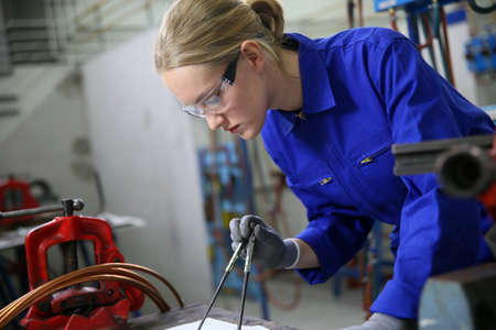 Photo for Young woman apprentice learning plumbing - Royalty Free Image