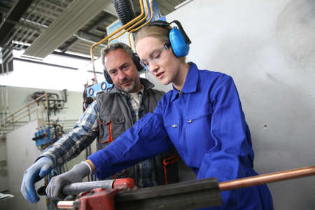 Photo for Young woman in professional training to become plumber - Royalty Free Image