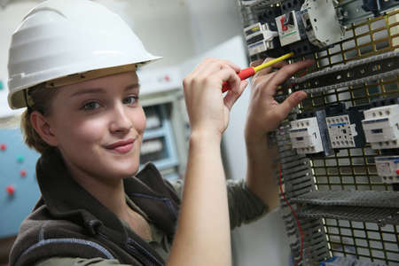Photo for Young woman in professional training setting up electrical circuit - Royalty Free Image