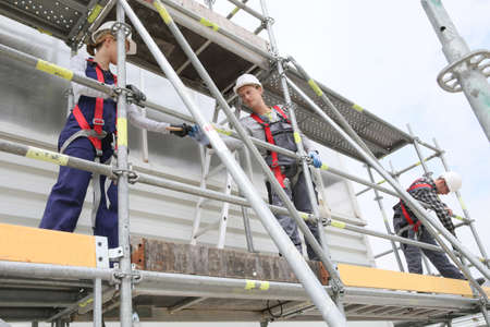 Photo pour Construction workers installing scaffolding on site - image libre de droit