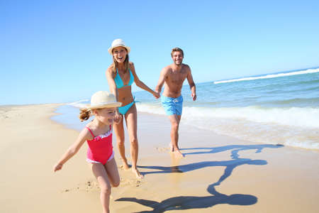 Photo pour Family having fun running on a sandy beach - image libre de droit