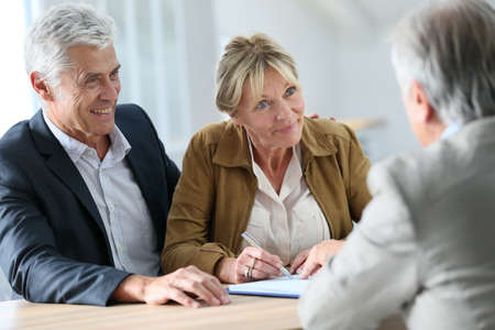 Foto de Senior couple meeting real-estate agent for investment - Imagen libre de derechos