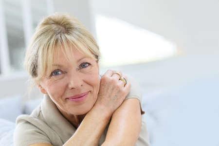 Photo pour Portrait of senior woman relaxing in couch - image libre de droit