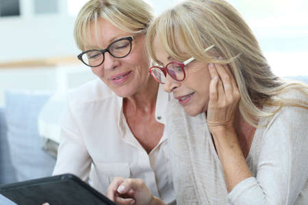Photo pour Senior women at home using digital tablet - image libre de droit