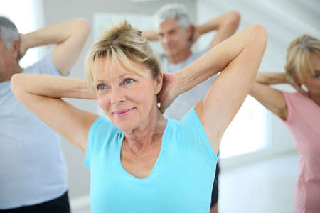 Foto de Senior people stretching out in fitness room - Imagen libre de derechos