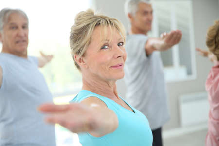 Photo pour Senior people stretching out in fitness room - image libre de droit
