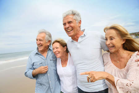 Photo pour Senior people walking on the beach - image libre de droit