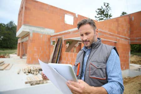 Foto de Engineer on construction site checking house building with blueprint - Imagen libre de derechos