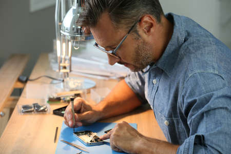 Photo pour Man repairing broken smartphone in workshop - image libre de droit