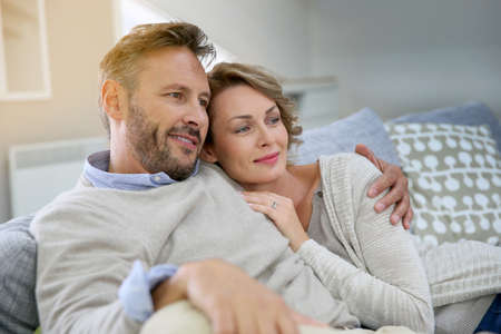 Photo pour Mature couple relaxing in couch at home - image libre de droit