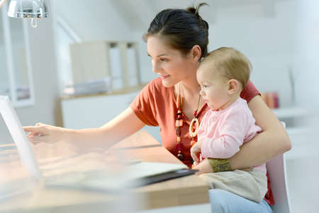 Photo pour Woman working from home with baby on lap - image libre de droit