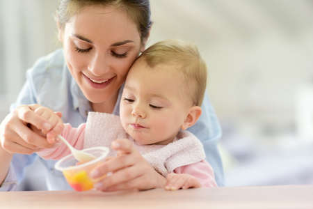 Photo pour Young mother helping baby girl with eating by herself - image libre de droit