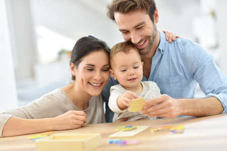 Photo for Parents with baby girl playing with wooden game - Royalty Free Image
