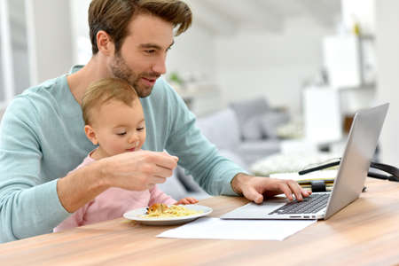 Photo pour Man working from home and taking care of baby - image libre de droit
