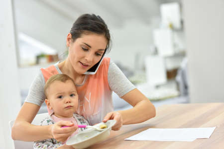 Photo pour Busy mother on the phone feeding baby a the same time - image libre de droit