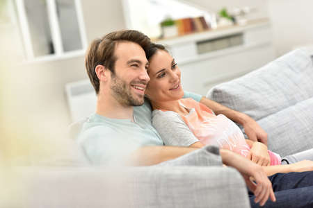 Photo pour Couple relaxing in sofa and watching tv - image libre de droit