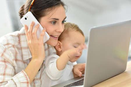 Foto de Busy young businesswoman working on laptop, baby on lap - Imagen libre de derechos