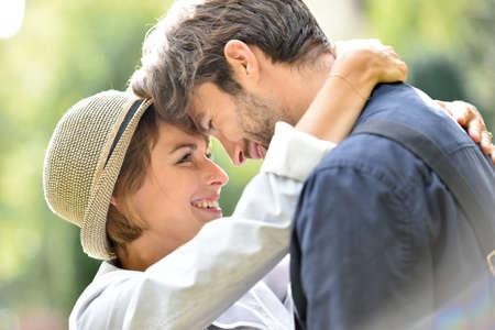 Photo pour Romantic young couple embracing in park, sunlight - image libre de droit