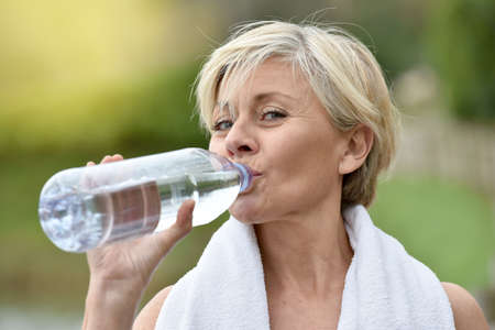 Photo for Senior woman drinking water after exercising - Royalty Free Image