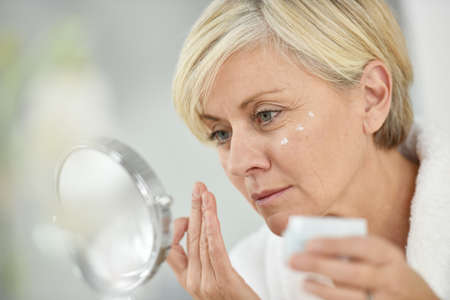 Photo pour Senior woman in bathroom applying anti-aging lotion - image libre de droit
