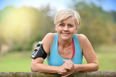 Photo pour Portrait of smiling senior woman relaxing after exercising - image libre de droit
