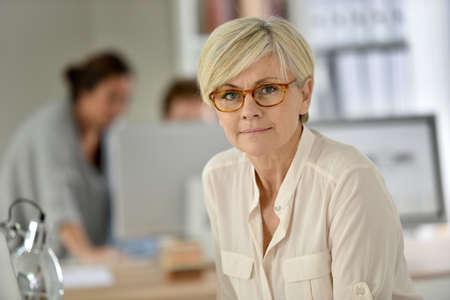 Photo pour Senior businesswoman standing in office - image libre de droit