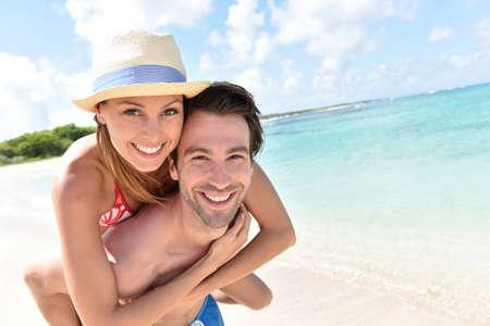 Photo pour Man giving piggyback ride to girlfriend on Caribbean beach - image libre de droit