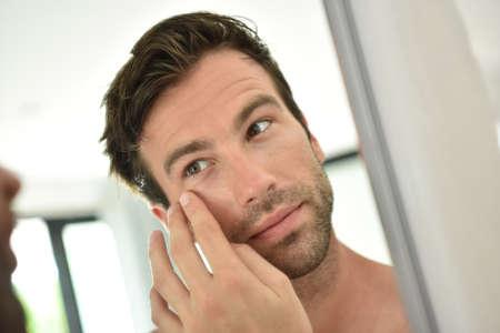 Photo pour Handsome man applying facial cream in front of mirror - image libre de droit