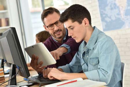 Foto de Teacher in computing class assisting teenager with tablet - Imagen libre de derechos
