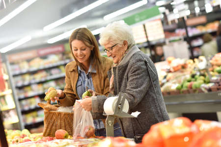 Photo for Elderly woman with young woman at the grocery store - Royalty Free Image