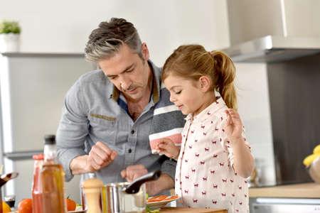 Foto de Father with little girl cooking together in kitchen - Imagen libre de derechos