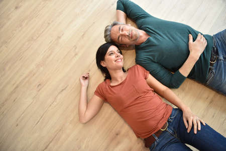 Foto de Upper view of couple laying on wooden floor - Imagen libre de derechos