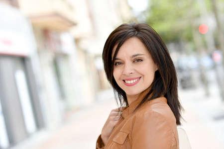 Photo pour Smiling active woman walking in street - image libre de droit