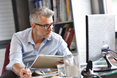 Photo for Businessman sitting in office working on tablet - Royalty Free Image