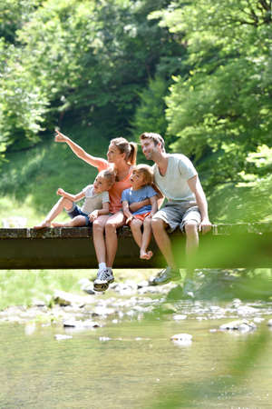 Photo for Family sitting on a bridge crossing mountain river - Royalty Free Image