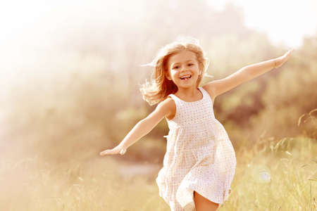 Foto de Little girl running in country field in summer - Imagen libre de derechos