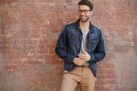 Photo pour Smiling trendy guy with blue jeans jacket and eyeglasses standing by brick wall - image libre de droit