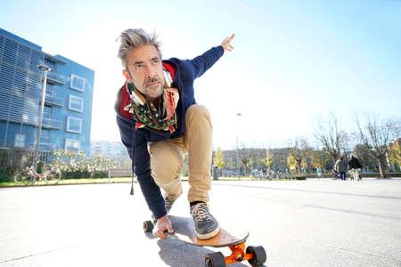 Photo pour Mature man skateboarding in the street - image libre de droit