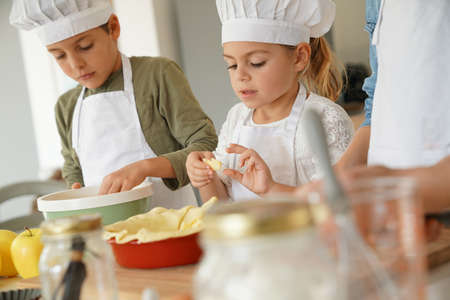 Photo pour Kids in cooking class workshop preparing apple pie - image libre de droit