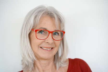 Foto de Portrait of senior woman with red shirt and eyeglasses, isolated - Imagen libre de derechos