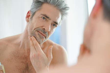Photo pour Portrait of mature man in front of mirror applying facial cream - image libre de droit