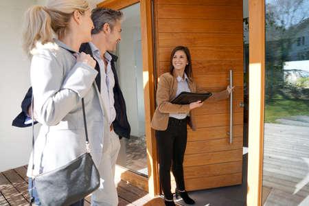 Photo pour Real estate agent inviting couple to enter house for visit - image libre de droit