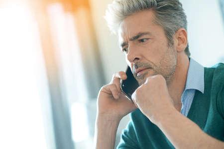Foto de Middle-aged man at home talking on phone - Imagen libre de derechos