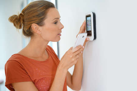 Photo pour Woman using smartphone to control home connectivity interface - image libre de droit