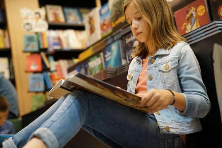 Foto de Young girl in book store reading comics - Imagen libre de derechos