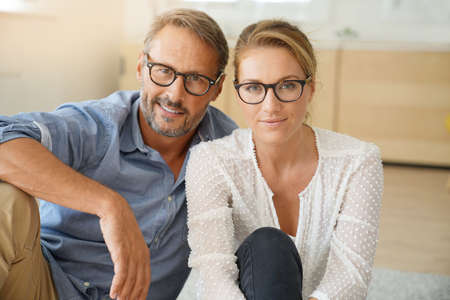 Photo for Mature couple with eyeglasses sitting on carpet at home - Royalty Free Image