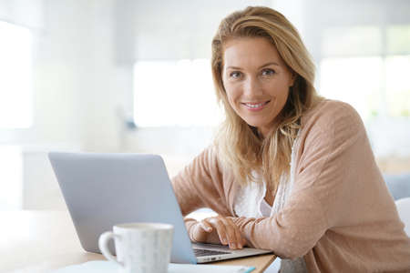 Photo for Attractive blond woman working on laptop computer at home - Royalty Free Image