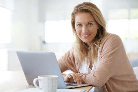 Foto de Attractive blond woman working on laptop computer at home - Imagen libre de derechos