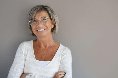 Photo pour Portrait of mature woman with eyeglasses on grey background - image libre de droit