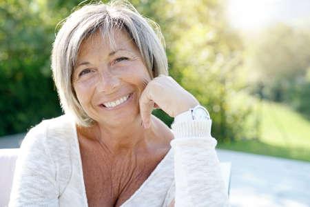 Photo pour Portrait of cheerful senior woman relaxing in outdoors sofa - image libre de droit